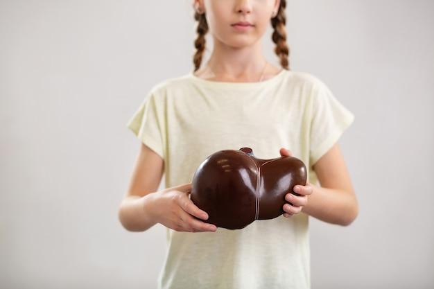 Anatomia człowieka. miła młoda dziewczyna trzymająca ludzką wątrobę, pokazując ci ją