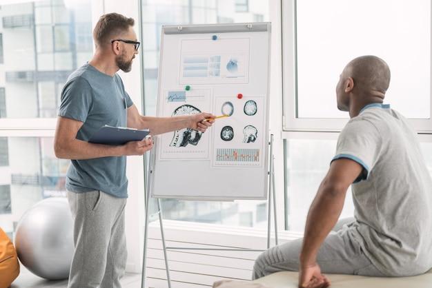 Anatomia człowieka. miły, inteligentny lekarz pokazujący swojemu pacjentowi zdjęcie, wyjaśniając anatomię człowieka