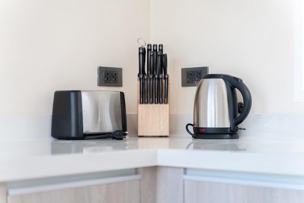 Aneks kuchenny składa się z tostera, czajnika i zestawu noży na blacie kuchennym