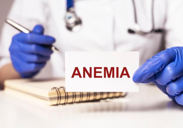 Anemia czerwone słowo na papierze w ręce lekarza in