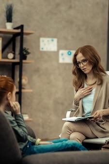 Angażująca rozmowa. radosny pozytywny psycholog uśmiechający się podczas rozmowy z pacjentem