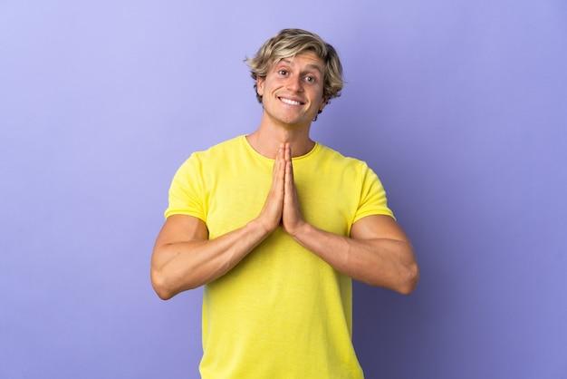 Angielski człowiek na białym tle fioletowe tło trzyma dłoń razem