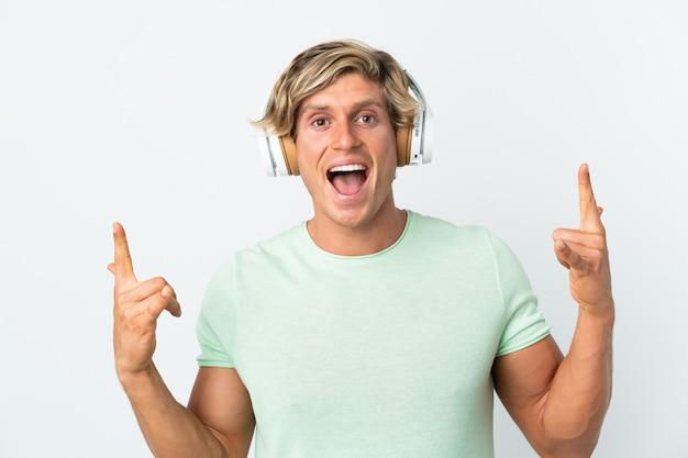 Angielski człowiek na białym tle słuchanie muzyki, czyniąc gest rocka
