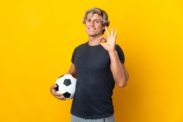Angielski człowiek na białym tle żółte tło z piłki nożnej i co znak ok