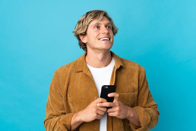 Angielski człowiek na na białym tle niebieską ścianą przy użyciu telefonu komórkowego i patrząc w górę