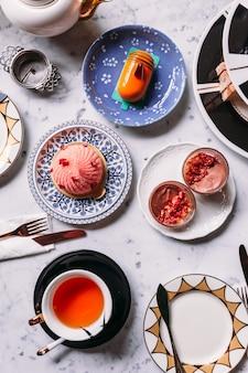Angielski podwieczorek obejmujący gorącą herbatę, ciasto, bułeczki, mus i sztućce