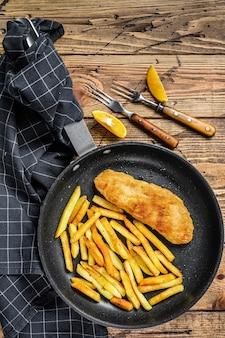 Angielski tradycyjne danie z rybą z frytkami na patelni. drewniane tło. widok z góry.