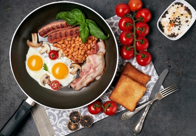 Angielskie śniadanie. jajka sadzone, kiełbaski, bekon, fasola, tosty, pomidory na kamiennym stole. widok z góry z miejscem na kopię