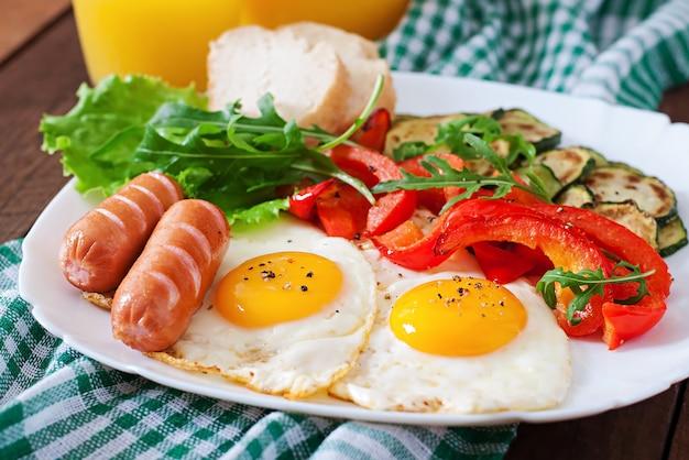 Angielskie śniadanie - jajka sadzone, kiełbaski, cukinia i słodka papryka