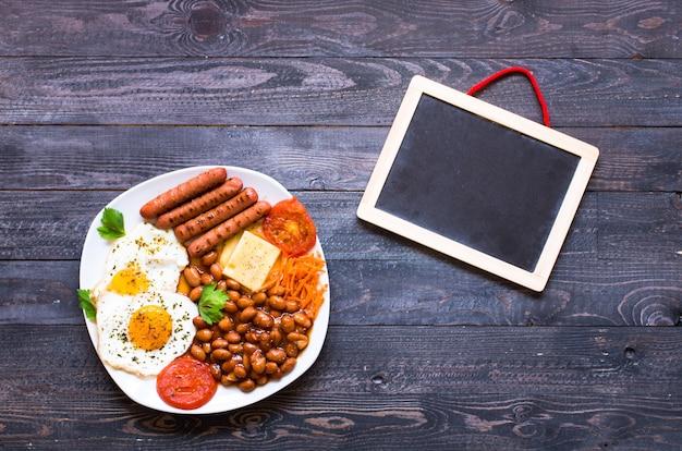 Angielskie śniadanie. jajka sadzone, kiełbaski, fasola, tosty chlebowe, pomidory, ser na drewnianej powierzchni,