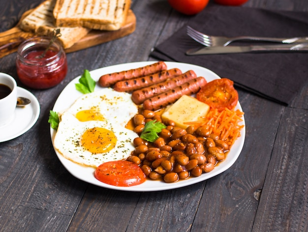 Angielskie śniadanie. jajka sadzone, kiełbaski, fasola, tosty chlebowe, pomidory, ser,