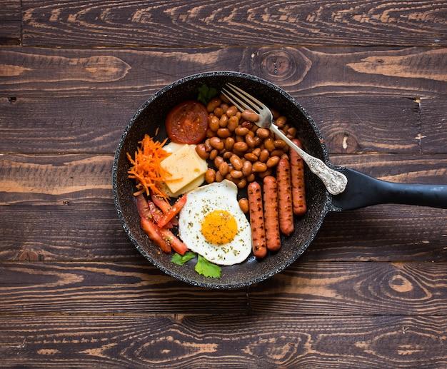 Angielskie śniadanie. jajka sadzone, kiełbaski, fasola, tosty chlebowe, pomidory