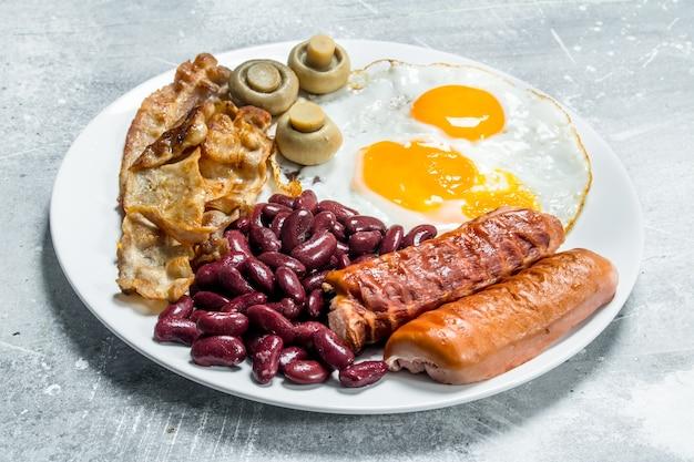 Angielskie śniadanie. jajka sadzone z kiełbasą, boczkiem i fasolą. na rustykalnej powierzchni.