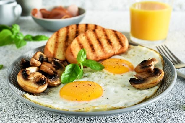 Angielskie śniadanie. jajka sadzone z pieczarkami i szynką ze szklanką soku pomarańczowego na śniadanie. dzień dobry.