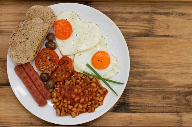 Angielskie śniadanie na białym talerzu na brązowym drewnianym stole