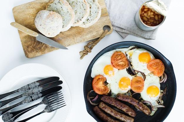Angielskie śniadanie na patelni na białym tle.