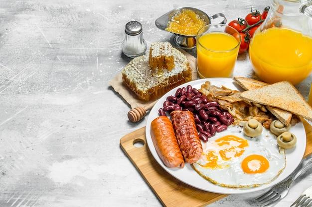 Angielskie śniadanie. różnorodne przekąski z sokiem pomarańczowym. na rustykalnej powierzchni.