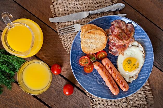 Angielskie śniadanie - tosty, jajko, bekon i warzywa w stylu rustykalnym na drewnianym stole