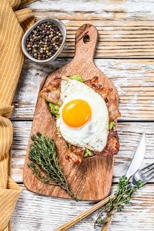 Angielskie śniadanie, tosty z boczkiem, awokado i jajkiem na desce do krojenia na białym drewnie. widok z góry
