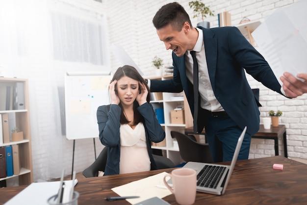 Angry irate boss krzyczy na pracownicę w ciąży