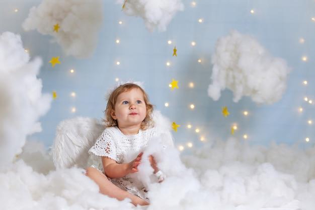 Anielskie dziecko siedzi chmury spogląda w dół