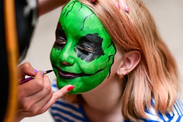 Animator rysuje zielone kolory na twarzy dziecka