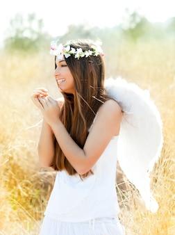 Anioł dziewczyna w złotym polu z piórkowymi białymi skrzydłami