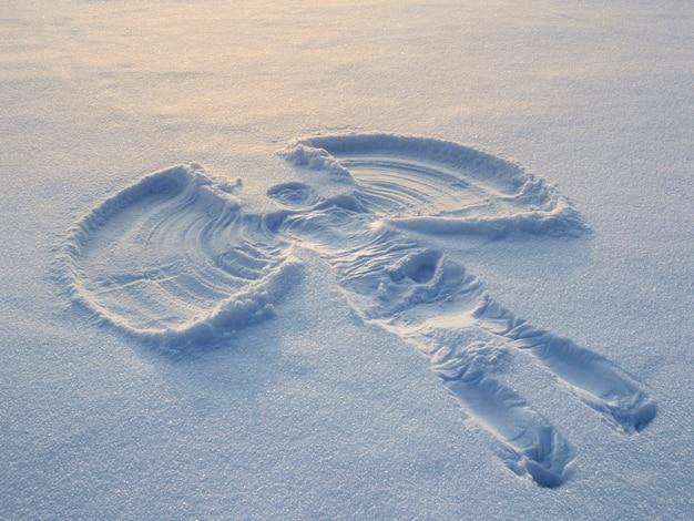 Anioł śnieżny wykonany wieczorem w białym śniegu. płaski widok z góry.
