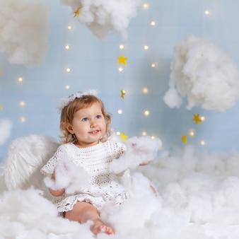 Aniołek dziecko siedzi w chmurach, patrząc w górę