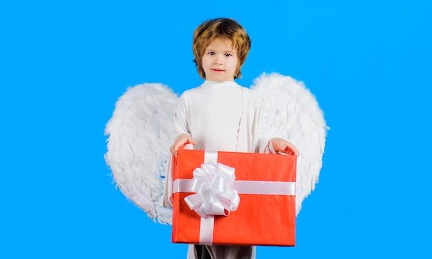 Aniołek z białymi skrzydłami z prezentem, chłopiec dzieciak w pudełku prezentowym, walentynki