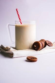 Anjeer lub figowy shake mleczny w szklanym słoiku z całymi suszonymi owocami na kolorowym lub drewnianym tle. selektywne skupienie