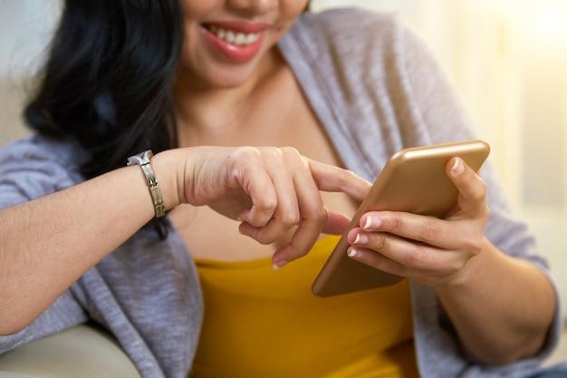 Anonimowa filipińska kobieta przeglądająca smartfon