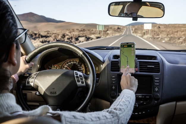 Anonimowa kobieta za pomocą mapy gps w smartfonie, aby wytyczyć trasę podczas jazdy samochodem podczas podróży na łonie natury