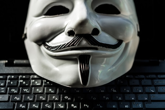 Anonimowa maska na klawiaturze laptopa. anonimowość w internecie. zdjęcie wysokiej jakości