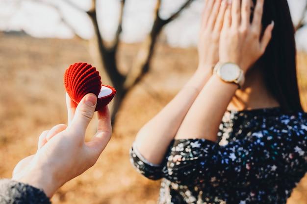 Anonimowa młoda dama zakrywająca twarz rękami, stojąc na łonie natury z przyciętą ręką z pudełkiem na pierścionek