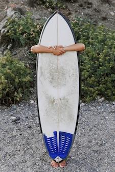 Anonimowa osoba przytulanie deskę surfingową na brzegu