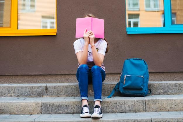 Anonimowa uczennica ukrywająca się za notatnikiem