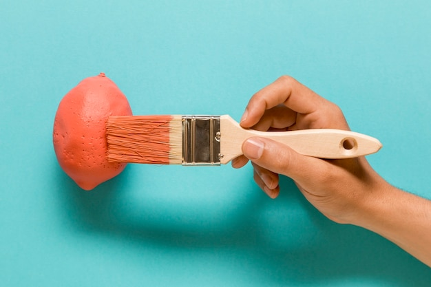 Anonimowy artysta maluje cytrynę w różowym kolorze