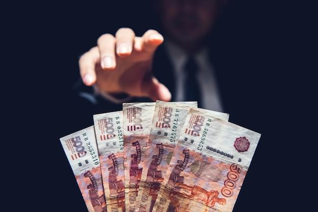 Anonimowy biznesmen wyciąga rękę po pieniądze, rosyjski rubel