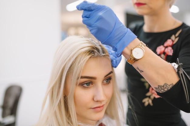 Anonimowy fryzjer farbujący włosy młodej blondynki
