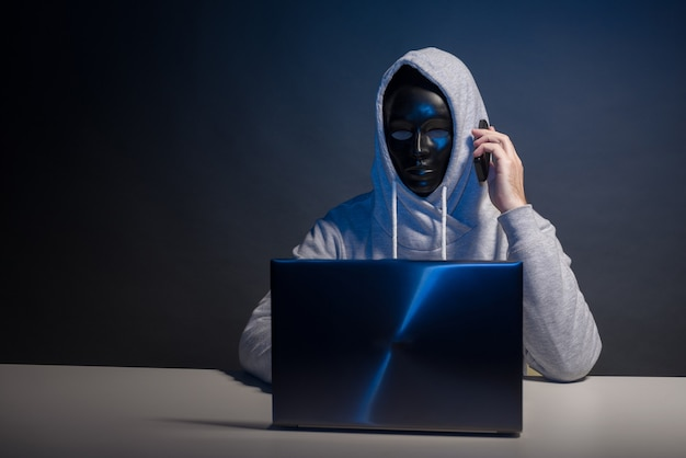 Anonimowy haker w masce programista używa laptopa i rozmawia przez telefon, aby włamać się do systemu w ciemności. pojęcie bazy danych cyberprzestępczości i hakowania