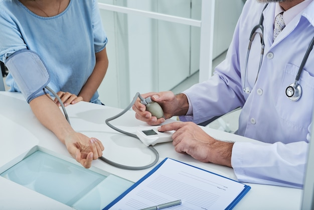 Anonimowy lekarz mierzący ciśnienie krwi u nieuznanego pacjenta za pomocą tonometru