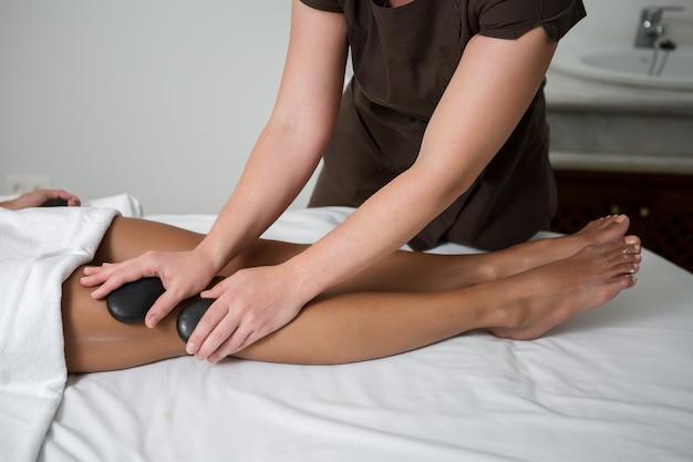 Anonimowy masażysta masujący gorącym kamieniem