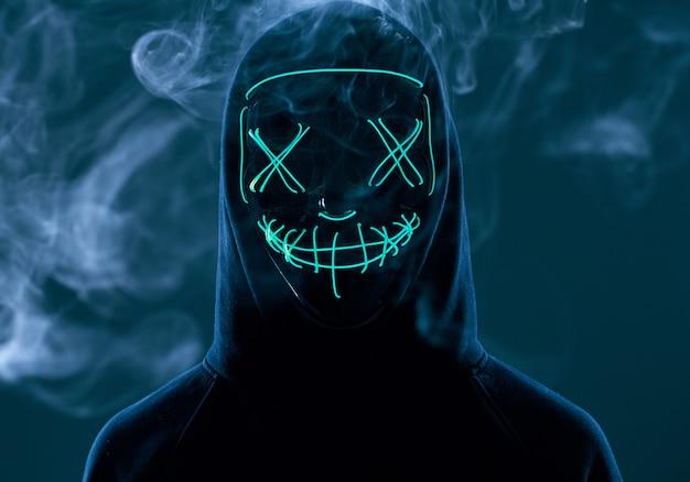 Anonimowy mężczyzna ukrywa twarz za neonową maską w kolorze dymu