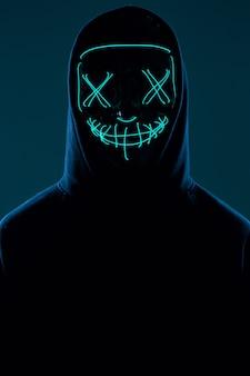 Anonimowy mężczyzna w czarnej bluzie z kapturem chowający twarz za neonową maską