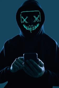 Anonimowy mężczyzna w czarnej bluzie z kapturem i neonowej masce włamujący się do smartfona
