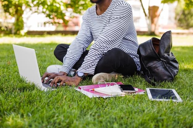 Anonimowy mężczyzna z komputerem w parku