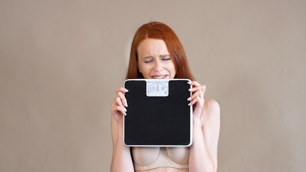 Anoreksyjna rudowłosa dziewczyna o smutnej twarzy trzyma skalę