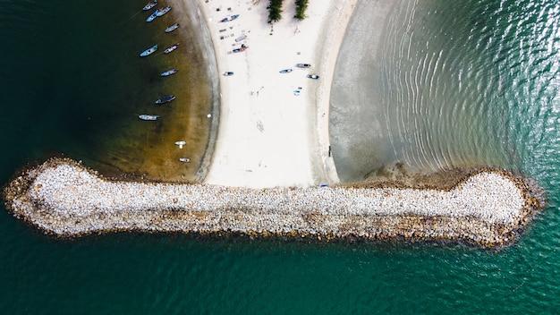 Antena falochronu plaża z widokiem grupy ludzi i małej łodzi rybackiej na białej, piaszczystej plaży, drzew i czystej wody morskiej.
