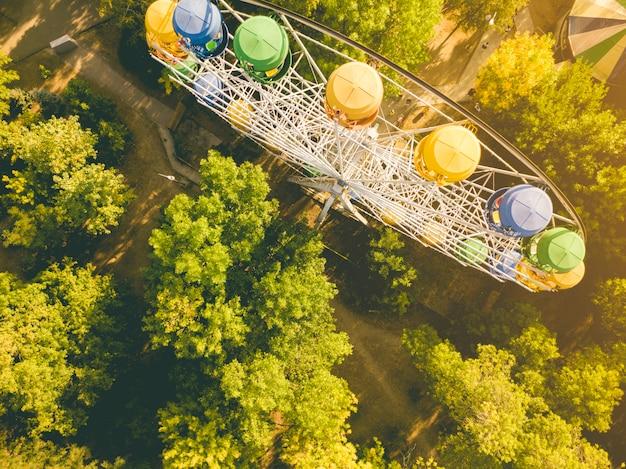 Antena góruje bezpośrednio nad widokiem diabelski młyn w lato rozrywki publicznym parku miejskim, dron strzelił d